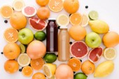 top view of bottles of fresh juice with ripe citrus fruits slices on white surface