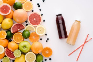 top view of various citrus fruits and blueberries with bottles of juice on white tabletop