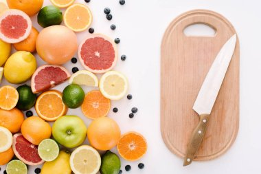 top view of citrus fruits with blueberries and wooden cutting board with knife on white surface