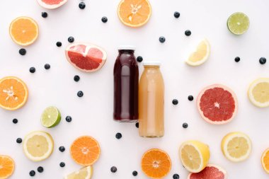top view of glass bottles of fresh juice with citrus fruits slices on white surface