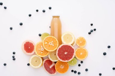 top view of bottle of juice with citrus fruits slices and blueberries on white surface