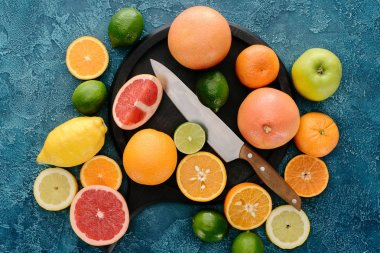 Top view of plate in shape of skillet and knife with citrus fruits slices on blue concrete surface stock vector