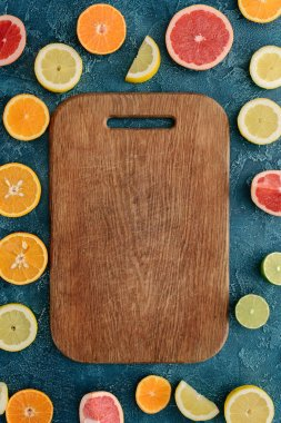 top view of wooden cutting board surrounded with citrus fruits slices on blue concrete surface