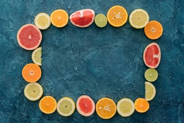 top view of frame made of citrus fruits slices on blue concrete surface