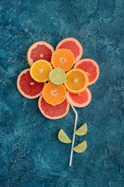 top view of flower composed with citrus fruits slices on blue concrete surface