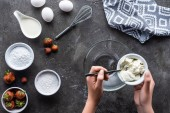 Fotografie partial view of woman putting sour cream into bowl while making cream for pie on dark grey surface
