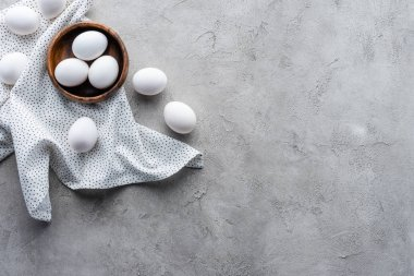 flat lay with raw chicken eggs in bowl and linen on grey tabletop