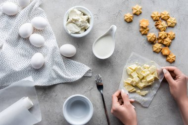 partial view of woman holding cut butter for pie with arranged ingredients around on grey tabletop