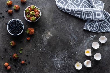 flat lay with fresh berries, eggshells and linen in dark grey surface