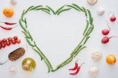 top view of heart made of fresh green peas and spices with ripe vegetables isolated on white