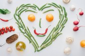 Photo top view of heart made of fresh green peas and asparagus and smiley face from tomatoes and chili peppers isolated on white