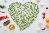 top view of heart made of fresh green peas and ripe vegetables isolated on white