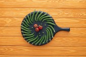 top view of fresh green peas and tomatoes on round board on wooden table top