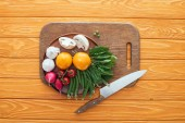 Photo top view of fresh raw vegetables in plate on wooden cutting board and knife on wooden table top