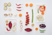 Photo top view of white plates and fresh sliced organic vegetables isolated on white