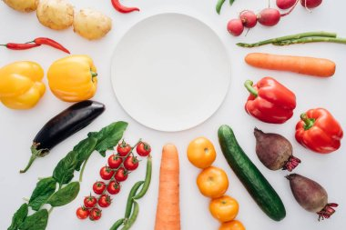 top view of empty round plate and fresh organic vegetables isolated on white