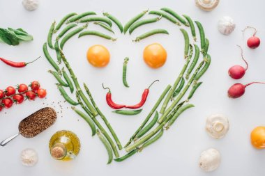 top view of heart made of fresh green peas and asparagus and smiley face from tomatoes and chili peppers isolated on white