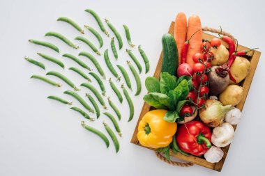 top view of box with fresh ripe vegetables and green peas isolated on white