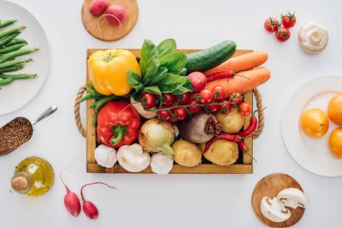 top view of box with fresh raw vegetables and plates isolated on white