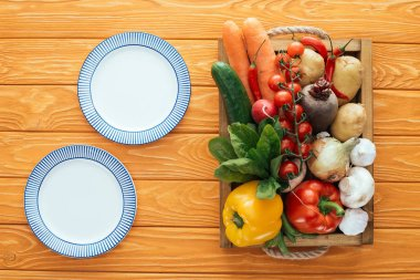 top view of empty round plates and fresh raw vegetables in box on wooden table top