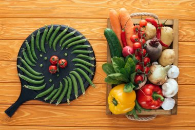 fresh green peas and tomatoes on round board and raw healthy vegetables in box on wooden table top