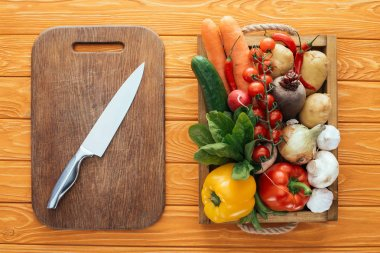 top view of wooden cutting board with knife and fresh raw vegetables in box on table top