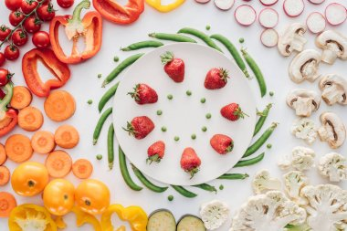 top view of fresh ripe strawberries and green peas on round white plate and organic vegetables isolated on white