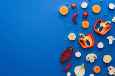 top view of raw sliced vegetables on blue background