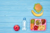 top view of tray with kids lunch for school, bottle of water and fruits on blue table