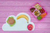 Photo top view of tray with kids lunch for school, burger and fruits on pink tabletop