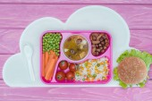 Photo top view of tray with kids lunch for school and burger on pink table