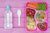 top view of tray with kids lunch for school and bottle of water on pink table