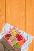 Fényképek top view of tray with kids lunch for school with napkins on orange wooden table