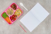 Photo top view of tray with kids lunch for school and open notebook on marble table