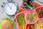 pohled shora tác s obědem dětí pro školu, budík a barevné tužky na stole