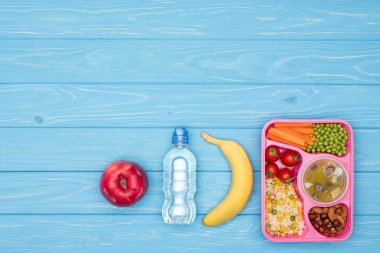 elevated view of tray with kids lunch for school, bottle of water and fruits on blue table
