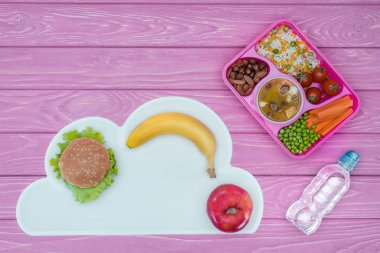 top view of tray with kids lunch for school, burger and fruits on pink table