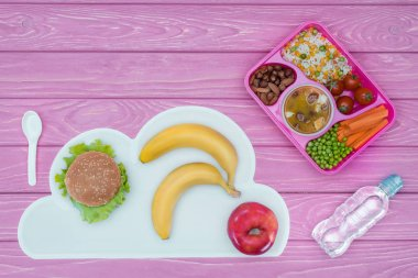 Top view of tray with kids lunch for school, burger and fruits on pink table stock vector