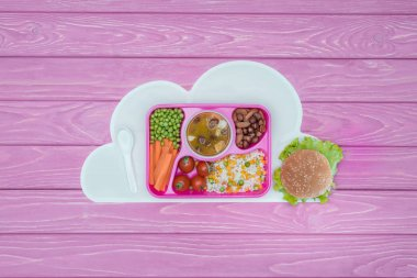 top view of tray with kids lunch for school and burger on pink table
