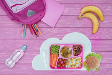 top view of tray with kids lunch for school, pink bag, pencils and bananas on pink table