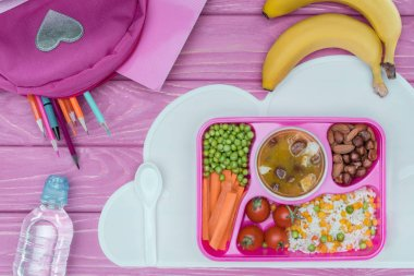 top view of tray with kids lunch for school, pink bag, pencils and bottle of water on pink table