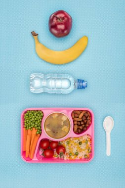 top view of tray with kids lunch for school, bottle of water, banana and apple on blue surface