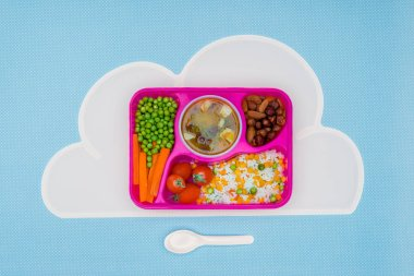 top view of tray with kids lunch for school on napkin isolated on blue