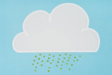 Top view of white napkin in shape of cloud with rain of green peas isolated on blue stock vector
