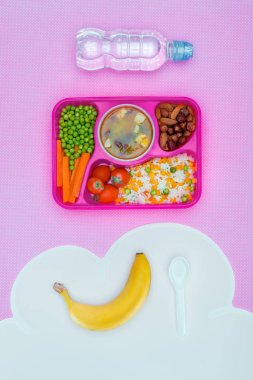 top view of tray with kids lunch for school, bottle of water and banana on violet table