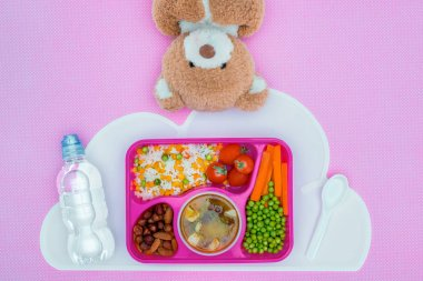 top view of tray with kids lunch for school and teddy bear on violet surface