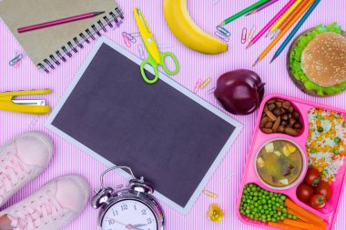 top view of blackboard and tray with kids lunch for school on purple tabletop