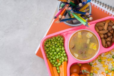 top view of tray with kids lunch for school and colored pencils on table