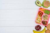 pohled shora tác s obědem dětí pro školu a ovoce na dřevěný stůl