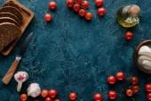Fotografia Pomodori rossi maturi con pane e spezie sul tavolo blu scuro
